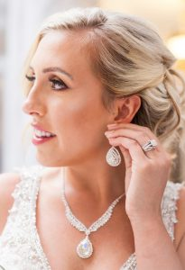 Engagement Ring Photo Showing Bride putting on her earring
